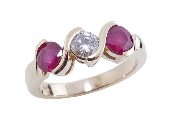14K yellow gold ring set with 2 = 0.93cttw rubies and a 0.279ct H, SI1 round brilliant cut diamond.