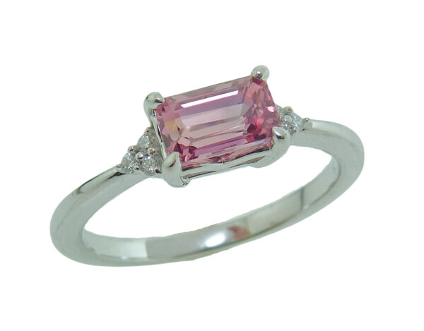 14 karat white gold ring featuring a 1.28ct oval emerald cut Padparadscha sapphire and accented with 6 = 0.05cttw of round brilliant cut diamonds.